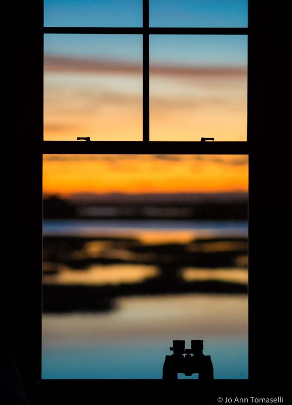 Silhouette of binoculars in window with colorful sky in background